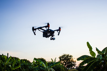 Professional camera drone flying in nature with clear sky.