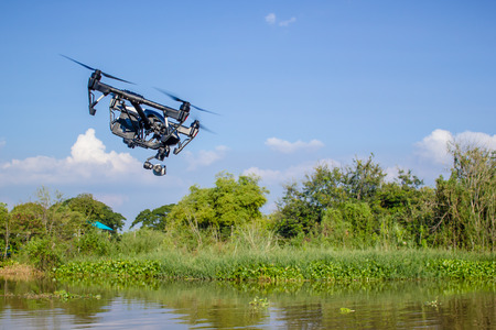 Professional camera drone fast flying on river.