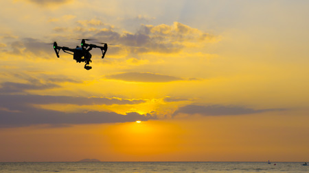 Professional camera drone flying on sea with sunset at twilight.