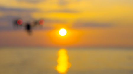 Blur for professional camera drone flying on sea with sunset at twilight. Stock Photo