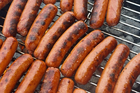 grill: All beef hot dogs on kettle style BBQ grill over a hot bed of coals.