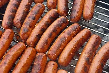 chorizos asados: Toda la carne de res hot dogs en estilo Hervidor barbacoa grill sobre una cama caliente de carbones. Foto de archivo