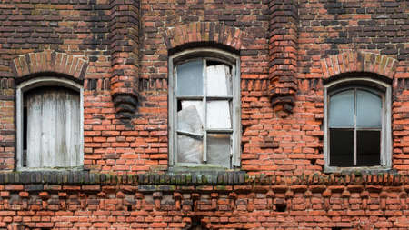 detail of an old weathered red brick wall with a wooden window frame weathered red brick wall with three wooden window frames