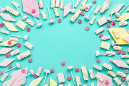 background, frame with marshmallows, sweets and lollipops on turquoise surface, copy space, top view, bright pastels theme