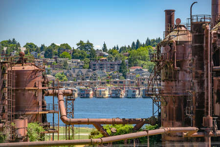 rust red: Abandoned machines and storage units in a gas industry at gas works park Seattle with water and homes. Machineries and storage units in a gas industry at gas works park Seattle Stock Photo
