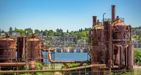 rust red: Abandoned machines and storage units in a gas industry at gas works park Seattle with homes behind. Machineries and storage units in a gas industry at gas works park Seattle Stock Photo