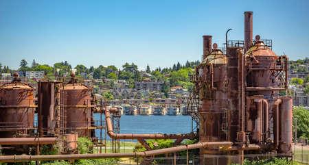 Verlassene Maschinen und Lagereinheiten in einer Gasindustrie im Gaswerk Park Seattle mit Häusern hinter. Maschinen und Speicher in einer Gasindustrie im Gaswerk Park Seattle Standard-Bild - 83911430