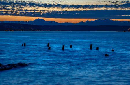 abandoned wooden pillars in the Tacoma bay. The bay in Tacoma Washington at sunset and into nightfall