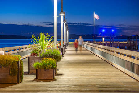 Rustic pier in Tacoma with unrecognizable couple . The bay in Tacoma Washington at sunset and into nightfall Stock Photo