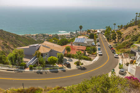Coastal views of homes in Laguna Beach California looking downhill in residencial neighborhood. Wide curved uphill road in Laguna Beach California during a sunny day on the coast