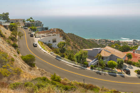 Coastal views of homes in Laguna Beach California. Coastal views of homes in Laguna Beach California. Wide curved uphill road in Laguna Beach California during a sunny day on the coast Stock Photo