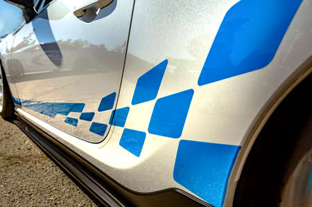 White car with blue strips and pattern closeup shot from the side. Various vehicle details in Southern California. Stock Photo