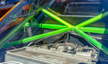 Green metal bars of a roll cage in the back of a car. Custom cars in Southern California summer 2017