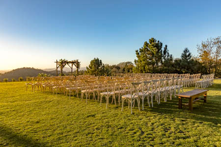 Golden hour of the wedding seating area from back with wider crop. Wonderful seating arrangement of an outdoor wedding in southern California. Flowers and ribbons on the chutzpah.  Stock Photo