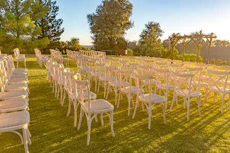 Golden hour of the wedding seating area from side. Wonderful seating arrangement of an outdoor wedding in southern California. Flowers and ribbons on the chutzpah.