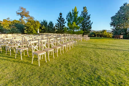Golden hour of the wedding seating area from front. Wonderful seating arrangement of an outdoor wedding in southern California. Flowers and ribbons on the chutzpah.  Stock Photo