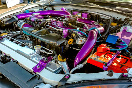 Purple pipes under the hood of modern car. Engine and other mechanical components of customized cars.