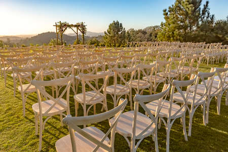 Golden hour of the wedding seating area from back.Wonderful seating arrangement of an outdoor wedding in southern California. Flowers and ribbons on the chutzpah.  Stock Photo
