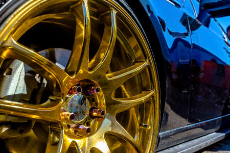 Golden rims on a black car looking very reflective. Various tires at a southern California event.