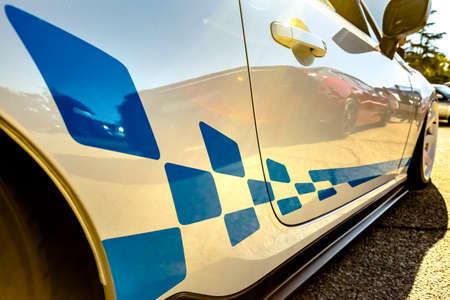 Wyścigowe naklejki na biały samochód ze złotym odbiciem na uchwycie samochodu. Różne szczegóły pojazdu w południowej Kalifornii.