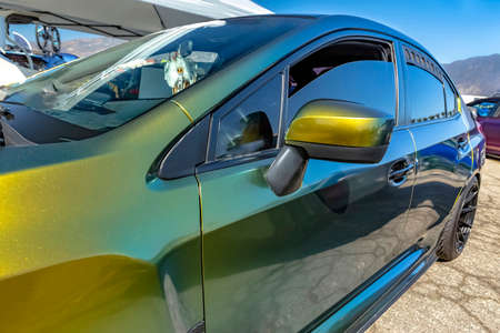 Green metallic car with tinted windows from the front drivers door. Custom cars in Southern California summer 2017