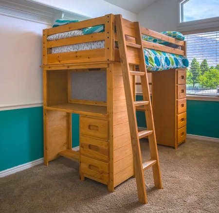 Wooden bunk bed in childs bedroom Фото со стока