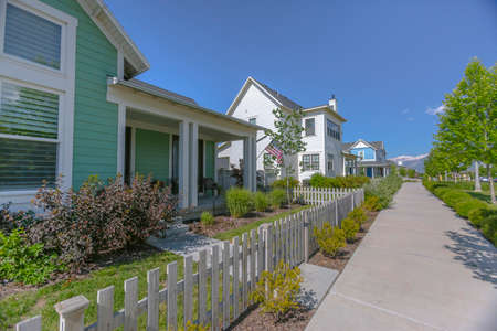 Green and white houses with public sidewalk Stock Photo