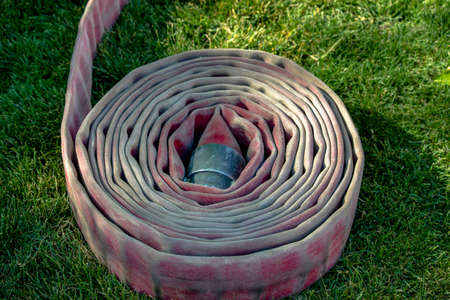 Single fire hose rolled up on grass