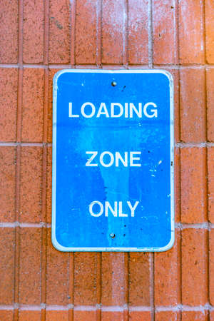 Loading zone only blue sign against brick Reklamní fotografie