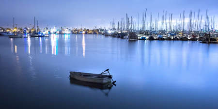 Boat in water with view of yachts and harbour 免版税图像