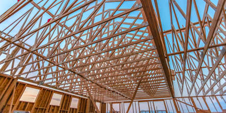 Guardando le nuove travi in legno di un edificio ampio pano