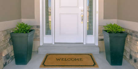 Front door with doormat plants and glass panel Stockfoto