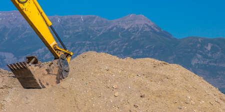 Excavator arm scooping dirt in front of mountain