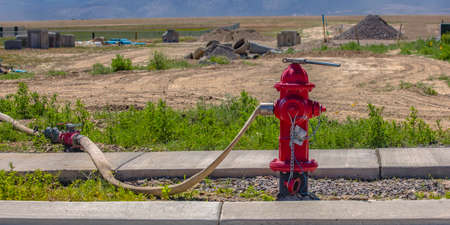 Red fire hydrant with connected hose and wrench Stockfoto