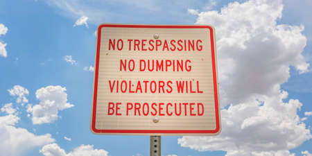 No trespassing sign against blue sky with clouds Stock Photo