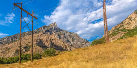 Power lines on a grassy hill in Provo Canyon Utah. Power lines on a hill with yellow grass in Provo Canyon. A rugged mountain beneath blue sky and clouds can be seen in the background.