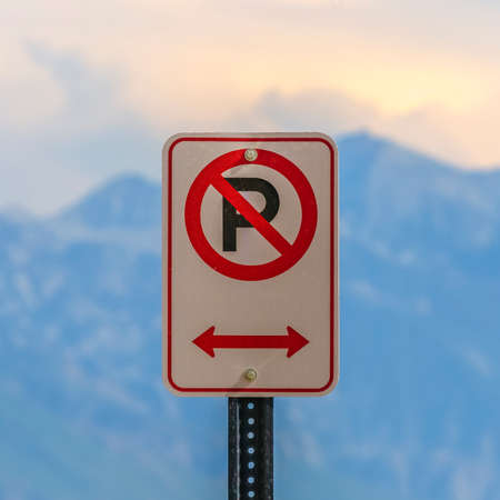 No parking sign against a blurry mountain and sky