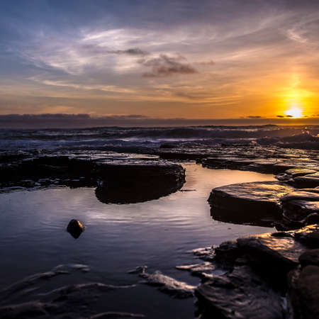 Tide pools with a dramatic sunset in San Diego Фото со стока