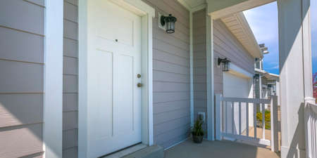 White front door and porch of home on a sunny day