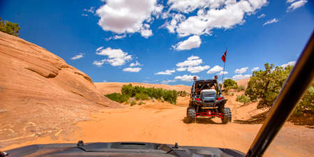 Off roading in Moab under blue sky with clouds Banco de Imagens