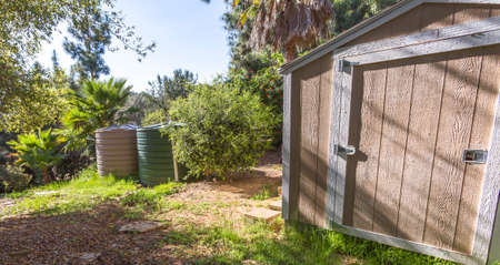 Wooden shed and cistern in a sunny backyard Stok Fotoğraf