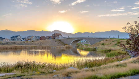 Bridge over Oquirrh Lake with golden sun in sky 스톡 콘텐츠