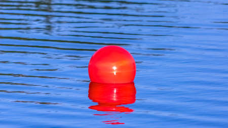 Bright red ball floating on the calm Oquirrh Lake