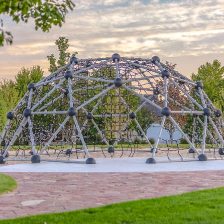 Dome climbing frame against trees homes and sky Stock Photo