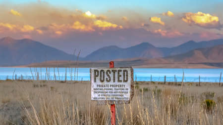 Posted sign against Utah Lake mountain and sky Imagens