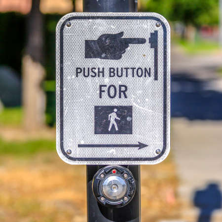 Push button for pedestrian crossing sign on a road