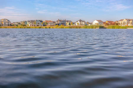 Rippling water of Oquirrh Lake with home and sky