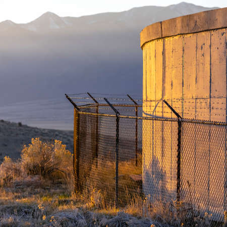 Concrete water tank barbed wire fence in mountains Stock Photo