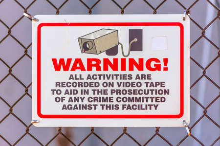 Warning security camera sign on a chain link fence Stock Photo