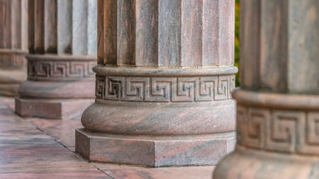 Columns with round base and vertical fluted shafts. Row of columns outside a building with geometric pattern design on the round bases. The shafts of the columns have vertical flutings on the surface.